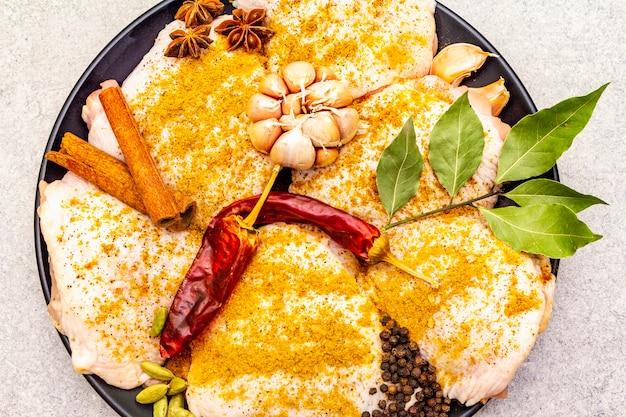 Coxas de frango cru com especiarias indianas tradicionais. mistura de curry amarelo, anis estrelado, cardamomo, louro, pimenta, alho, canela. ingredientes para cozinhar em uma superfície de pedra, close-up, vista superior, macro.