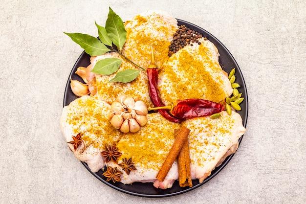 Coxas de frango cru com especiarias indianas tradicionais. mistura de curry amarelo, anis estrelado, cardamomo, louro, pimenta, alho, canela. ingredientes para cozinhar em uma superfície de pedra, close-up, vista superior.