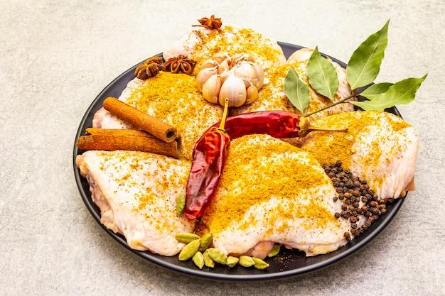 Coxas de frango cru com especiarias indianas tradicionais. mistura de curry amarelo, anis estrelado, cardamomo, louro, pimenta, alho, canela. ingredientes para cozinhar em uma superfície de pedra, close-up.