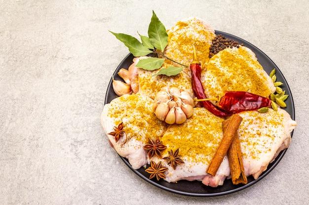 Coxas de frango cru com especiarias indianas tradicionais. mistura de curry amarelo, anis estrelado, cardamomo, louro, pimenta, alho, canela. ingredientes para cozinhar em uma superfície de pedra, copie o espaço, vista superior.