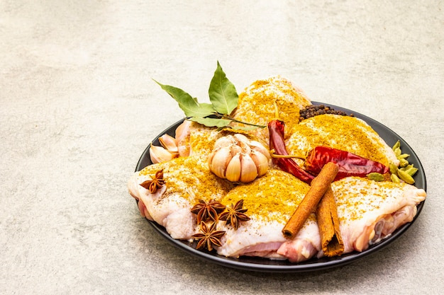 Coxas de frango cru com especiarias indianas tradicionais. mistura de curry amarelo, anis estrelado, cardamomo, louro, pimenta, alho, canela. ingredientes para cozinhar em uma superfície de pedra, copie o espaço.
