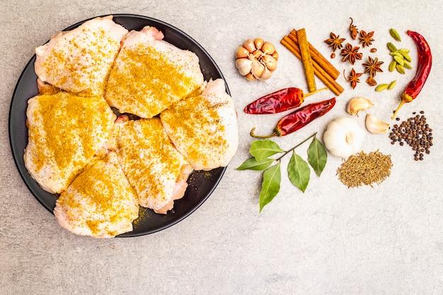 Coxas de frango cru com especiarias indianas tradicionais. mistura de curry amarelo, anis estrelado, cardamomo, louro, pimenta, alho, canela. ingredientes para cozinhar em uma superfície de pedra, vista superior.
