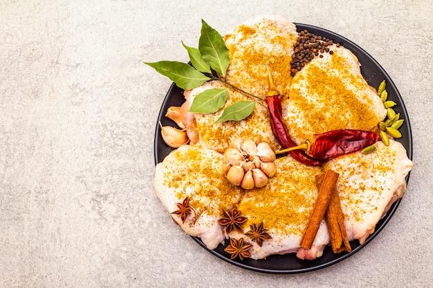 Coxas de frango cru com especiarias indianas tradicionais. mistura de curry amarelo, anis estrelado, cardamomo, louro, pimenta, alho, canela. os ingredientes para cozinhar na superfície da pedra fecham-se acima do espaço da cópia da vista superior.