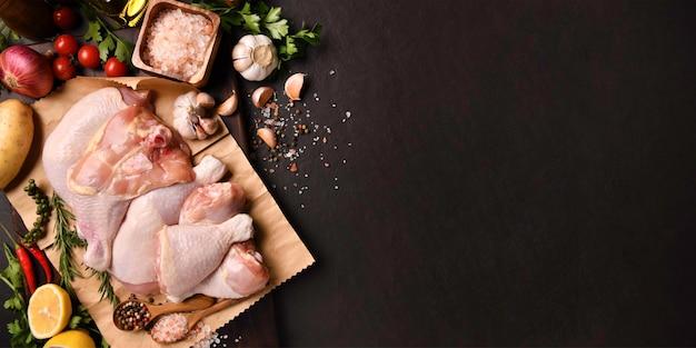 Coxas de frango cru e coxas de frango com ingredientes para cozinhar na superfície de pedra preta