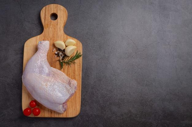 Coxas de frango cru na superfície de madeira escura.