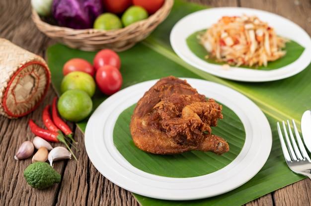 Coxas de frango frito em folhas de bananeira em um prato branco