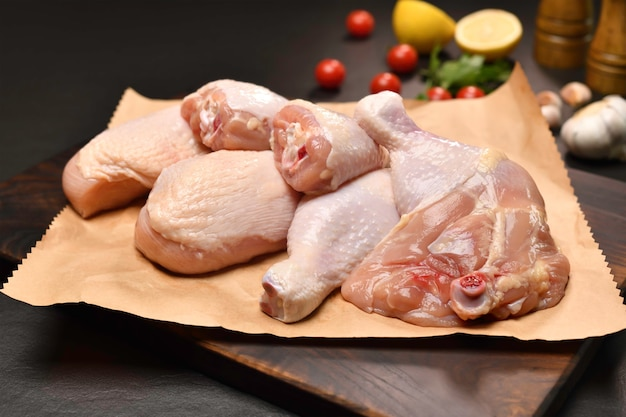 Coxas e pernas de frango frescas e cruas para cozinhar em um papel de embrulho com ingredientes na tábua de cortar