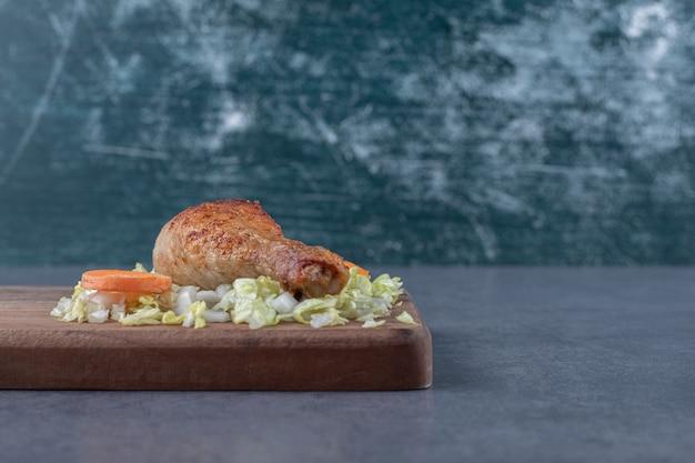 Coxinha de frango e legumes fatiados na placa de madeira.