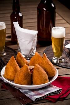 Coxinha, um petisco brasileiro, com um bar ao fundo.