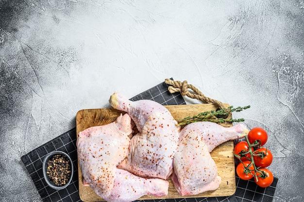 Coxinhas de frango cru com coxas, ervas frescas, cozinhar. superfície cinza. vista do topo. copie o espaço