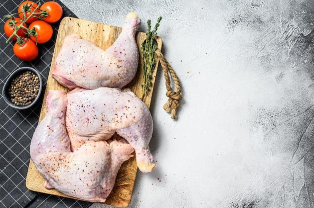 Coxinhas de frango cru com coxas, ervas frescas, cozinhar. vista do topo. copie o espaço