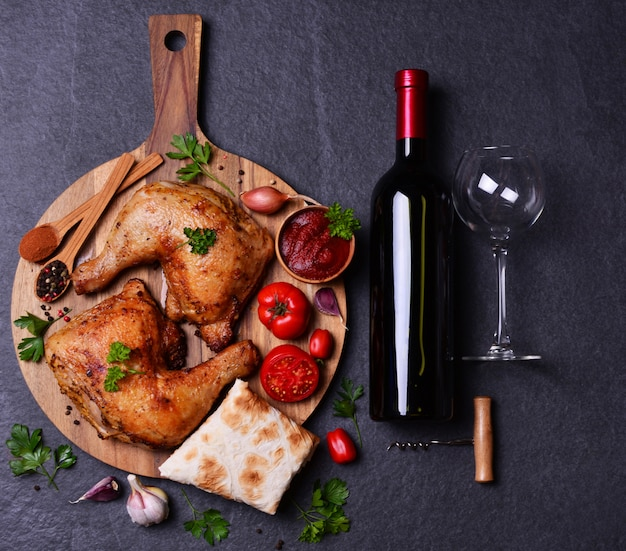 Coxinhas de frango grelhado com especiarias e legumes, com uma garrafa de vinho tinto.