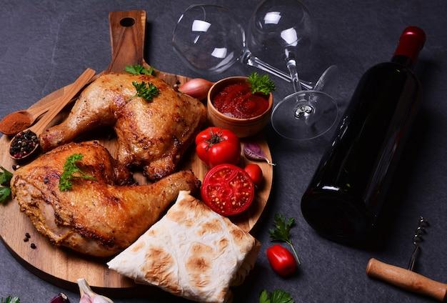 Coxinhas de frango grelhado com temperos e vegetais, acompanhado de uma garrafa de vinho tinto