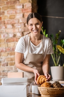 Cozedura, embalagem. mulher arrumada sorridente alegre com avental bege colocando croissant em uma caixa de produtos de embalagem na confeitaria