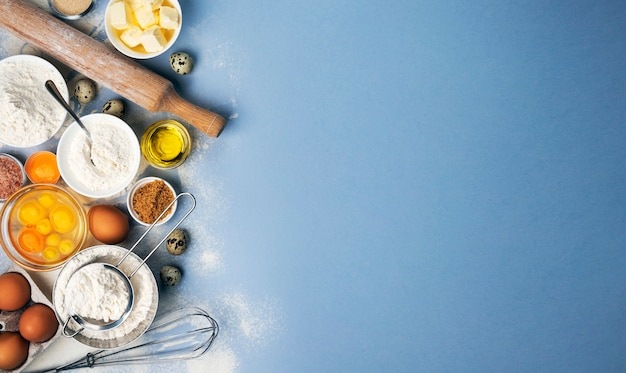 Cozer os ingredientes para a massa em azul, vista superior de farinha, ovos, manteiga, açúcar e utensílios de cozinha para assar caseiro com espaço de cópia de texto