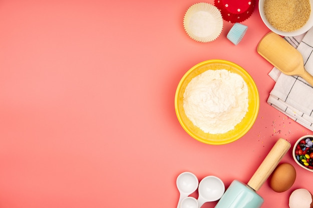 Cozer ou cozinhar ingredientes no fundo rosa, plana leigos