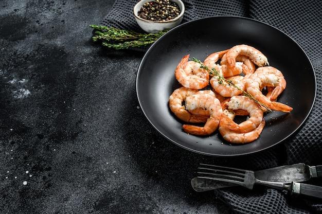 Cozido de camarão descascado, camarão em um prato. fundo preto.