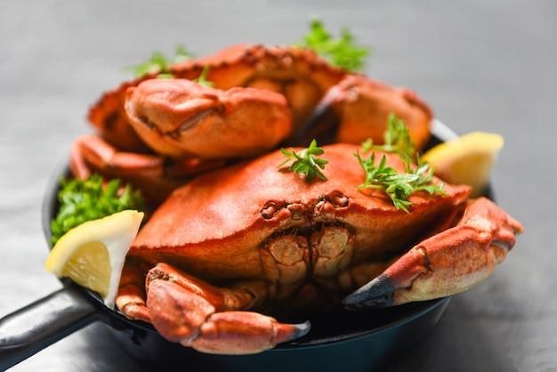 Cozido de caranguejo na panela quente e escuro, frutos do mar cozido caranguejos de pedra vermelha