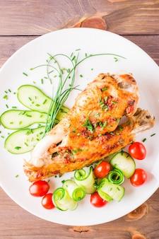 Cozido em uma asa de peru de especiarias, fatias de pepino e tomate cereja em um prato sobre uma mesa de madeira. vista do topo