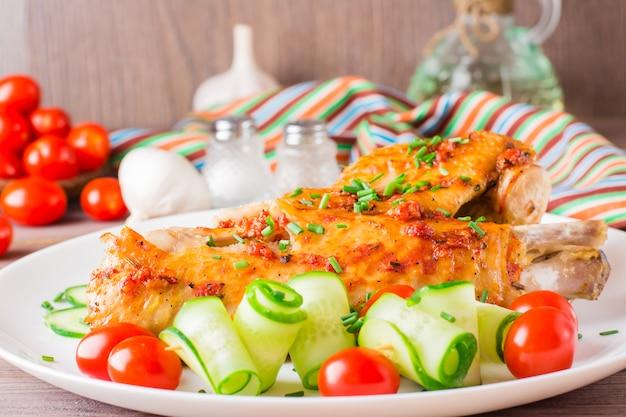 Cozido em uma asa de peru de especiarias, fatias de pepino e tomate cereja em um prato sobre uma mesa de madeira