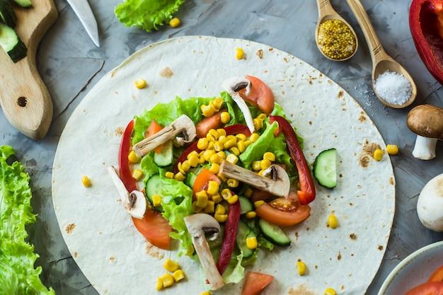 Cozimento burrito vegano mexicano - legumes e cogumelos em tortillas