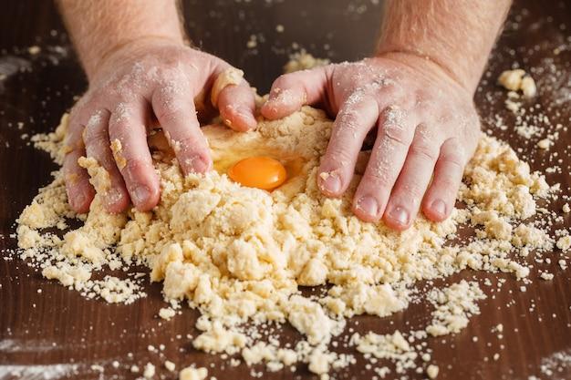 Cozimento caseiro, cena da cozinha, mostrando sementes de manteiga, farinha, açúcar e baunilha sendo misturadas para fazer biscoitos de biscoito amanteigado, com as mãos do homem.