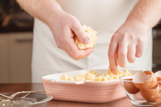 Cozimento caseiro, cena de cozinha mostrando sementes de manteiga, farinha, açúcar e baunilha sendo misturadas para fazer biscoitos de biscoito amanteigado, com mãos masculinas.