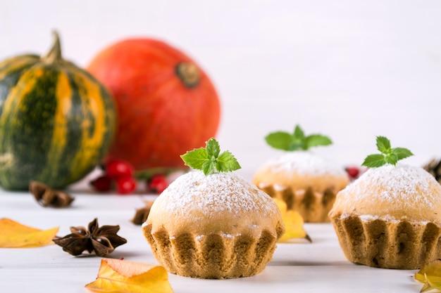 Cozimento caseiro em estilo outono. bolinhos deliciosos em uma placa de madeira com paus de canela, estrelas de anis, abóboras e bagas de rosa mosqueta. na mesa branca
