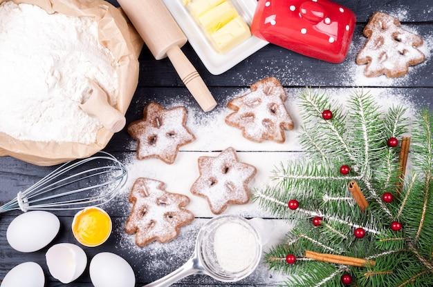 Cozimento de natal com cortadores de farinha, ovos, manteiga, framboesas, leite, canela, rolo, batedor e biscoito