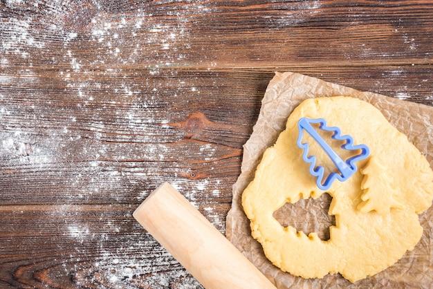 Cozimento de natal de biscoitos de gengibre em fundo escuro de madeira com galhos de pinheiro.