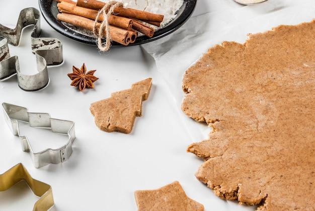 Cozimento de natal massa de gengibre para homens de gengibre estrelas de gengibre árvores de natal rolo de massa especiarias (canela e anis) farinha na cozinha da casa mesa de mármore branco