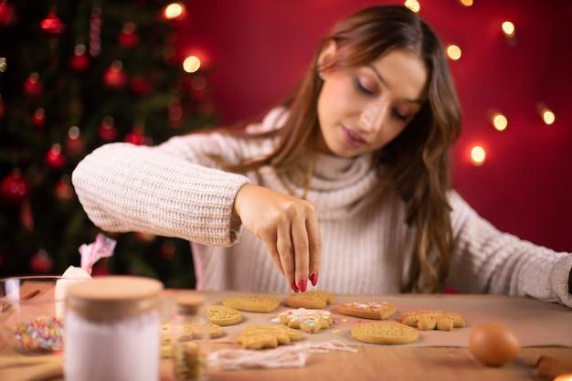Cozimento de natal. mulher jovem e bonita fazendo biscoitos de natal, para decorar a padaria de gengibre caseiro com granulado de açúcar. padaria artesanal de ano novo, feriado de inverno em casa, sobremesa culinária, tradição sazonal
