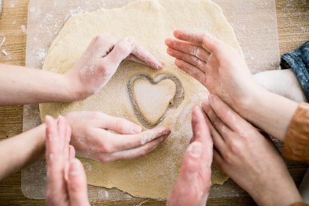 Cozimento e conceito home - próximo acima das mãos fêmeas que fazem cookies da massa fresca em casa. mãos de três mulheres segurar biscoito em forma de coração