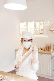 Cozimento pelo chef com a máscara médica. uma mulher com um chapéu branco com um rolo de massa na cozinha