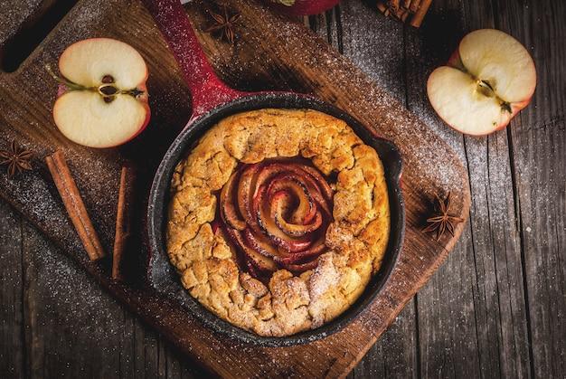 Cozimento tradicional do outono, receitas de ação de graças, torta caseira integral de galette de maçã com maçãs orgânicas e canela, na panela de ferro fundido, mesa de madeira velha, vista superior