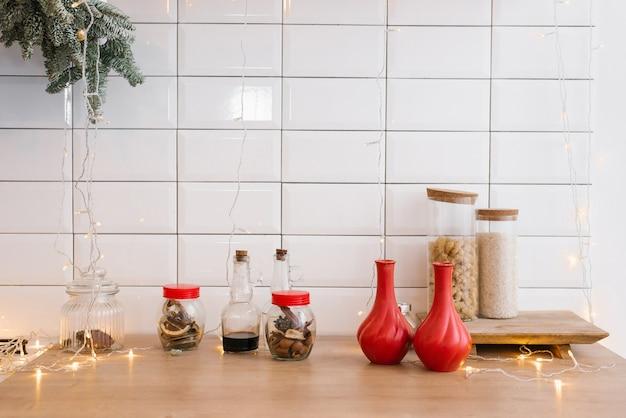Cozinha aconchegante de inverno com enfeites vermelhos, mesa e utensílios de natal