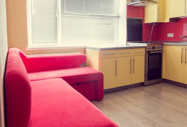 Cozinha amarela com armários, janela, laminado e sofá macio vermelho
