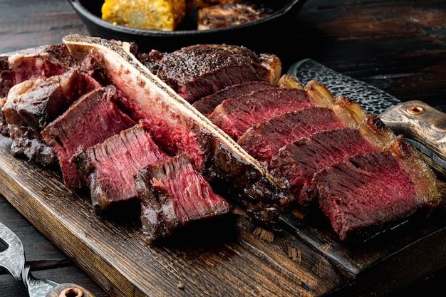 Cozinha americana. t-bone fatiado e assado ou carne porterhouse carne mal passada conjunto de bife, numa tábua de servir de madeira, na velha mesa de madeira escura