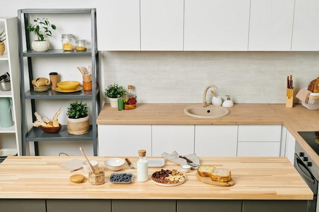 Cozinha ampla e moderna com utensílios de cozinha nas prateleiras, armários brancos nas paredes, comida e leite na mesa de madeira