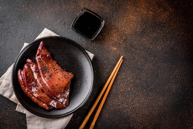 Cozinha asiática, iguarias. fígado de bovino cru com molho teriyaki e gergelim preto, vista de mesa enferrujada escura