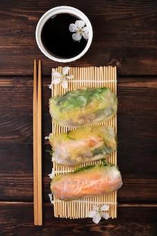 Cozinha asiática, rolinhos primavera com molho de soja e flores de cerejeira