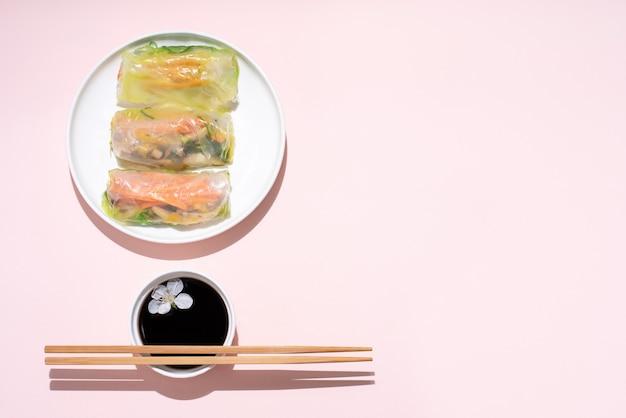Cozinha asiática, rolinhos primavera em um prato branco com flores de cerejeira e pauzinhos em um rosa