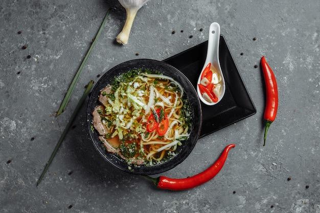 Cozinha asiática, sopa de carne em prato preto