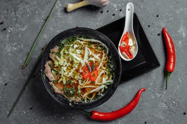 Cozinha asiática, sopa de carne em um prato preto sobre fundo escuro