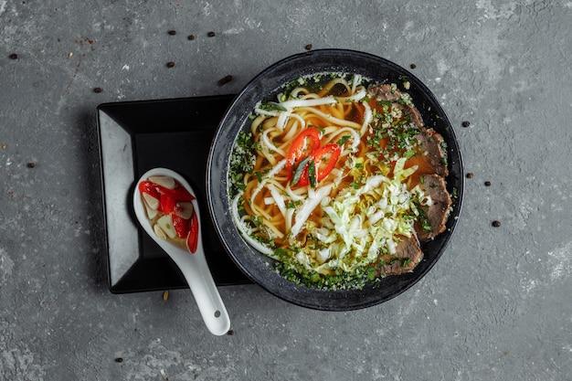 Cozinha asiática, sopa de carne fo em uma placa preta no escuro. sopa fo com caldo de carne picante, lombo de vaca, macarrão udon, pasta de pimenta, repolho de pequim, pimenta, coentro, molho picado