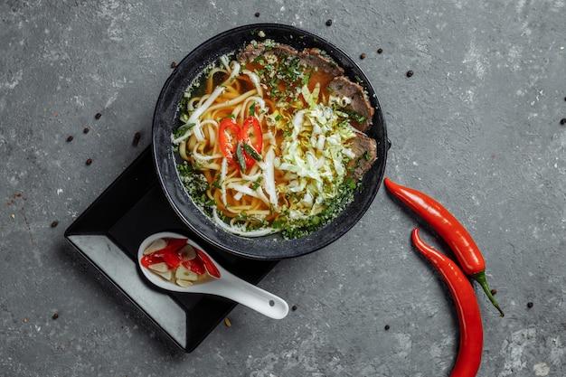 Cozinha asiática, sopa de carne fo em uma placa preta sobre uma mesa escura. sopa fo com caldo de carne picante, lombo de vaca, macarrão udon, pasta de pimenta, repolho de pequim, pimenta, coentro, molho picado