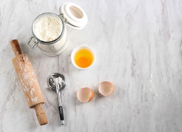 Cozinha bagunçada, após a preparação do forno na mesa de mármore. cortador de farinha, alfinete, ovo e pizza com espaço de cópia para texto
