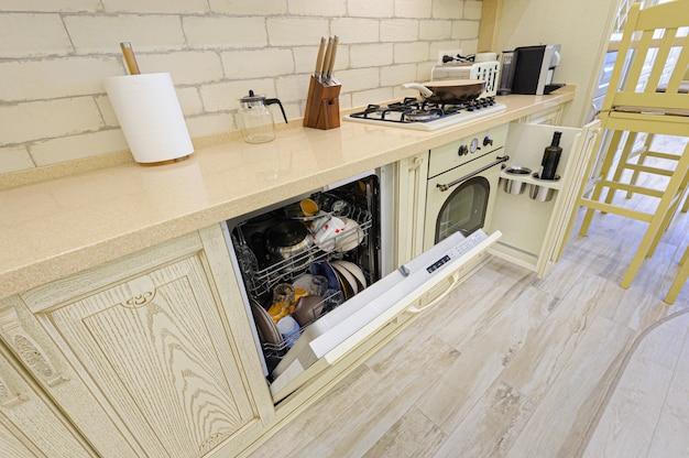 Cozinha bege moderna de luxo closeup, algumas gavetas abertas