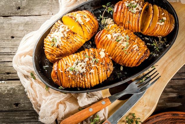 Cozinha caseira tradicional americana. a dieta vegana. batata caseira hasselback com ervas frescas e queijo. na mesa de madeira velha, copie o espaço