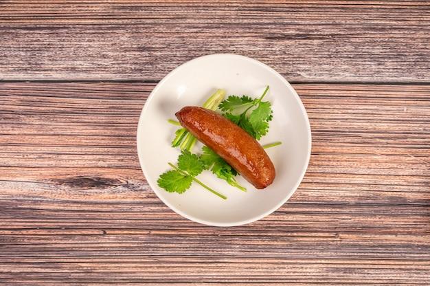Cozinha chinesa, salsicha no prato está na mesa de madeira